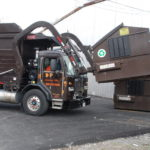 A front-load truck emptying container in Ashland, MA