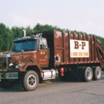 Side view of a garbage truck from B-P Trucking, Inc. waste removal service in Ashland, MA